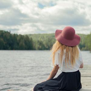 水辺に佇む帽子を被った女性