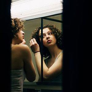 鏡でメイクをチェックしている女性