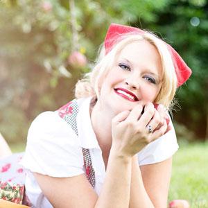 笑顔でこちらを見つめる金髪の女性