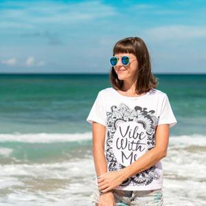 サングラスをかけて浜辺に佇む女性