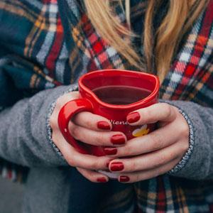 ハート型のカップを手に持つ女性