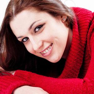 真っ赤なセーターを着ている笑顔の女性