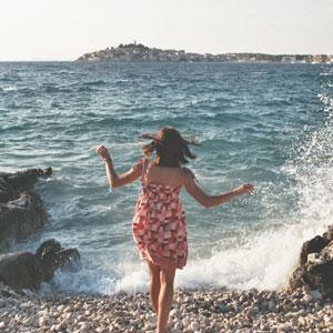 海辺にいるワンピース姿の女性