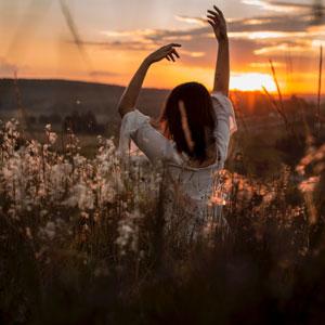 草原で両手を挙げている女性