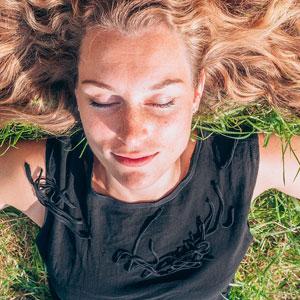 芝生の上に寝転んでいる女性