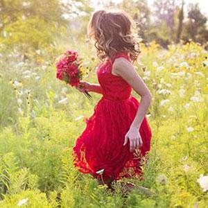 草原に佇む赤いドレスを着た女性