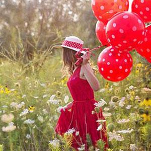 沢山の風船を手に持っている女性