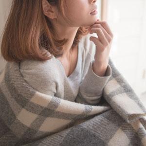 チェックの布を羽織っているミディアムボブの女性