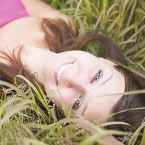 叢に寝転びながら微笑んでいる女性