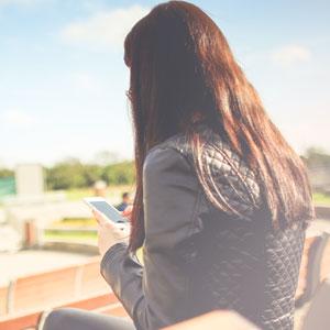 屋外のベンチでスマホを操作している女性