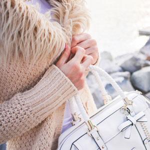 お洒落な白いバッグを手に持つ女性