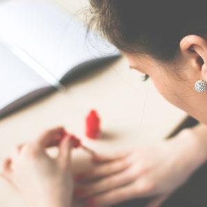赤いネイルを小指に塗っている女性