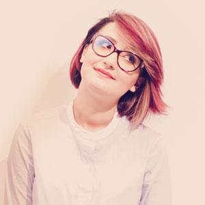 首を傾げている眼鏡が似合う女性
