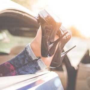 車の窓から黒いハイヒールをはいた足を放り出している女性