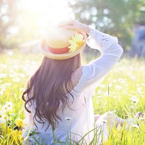 お花畑の中に座っている女性の後ろ姿